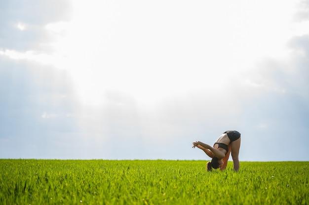 Treino matinal. conceito de estilo de vida saudável. jovem mulher atraente em roupas esportivas faz esticar a mão antes de treinar na natureza ao amanhecer. aquecimento muscular