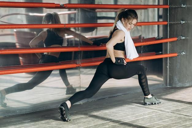 Treino matinal de treinamento de mulher no ginásio. jovem mulher fazendo exercícios de ginástica no ginásio