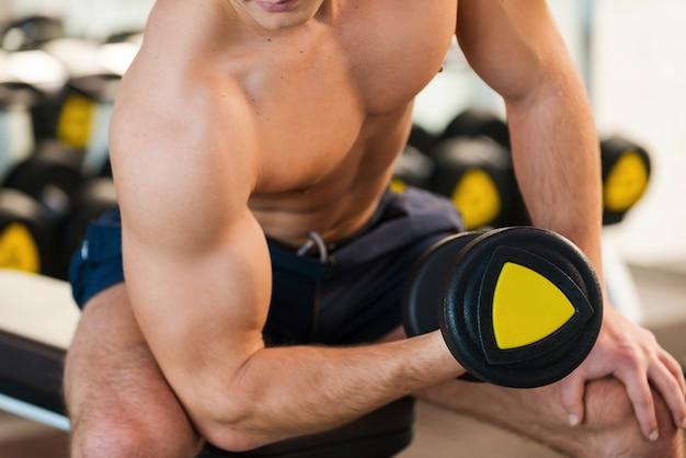 Treino no ginásio. close-up de jovem musculoso treinando com halteres na academia