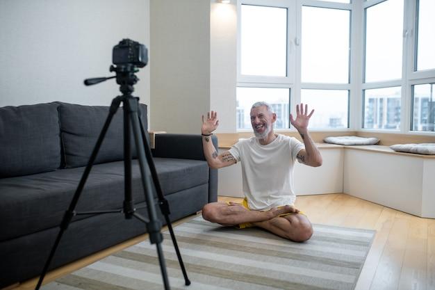 Treino online. um homem maduro de camiseta branca praticando ioga online