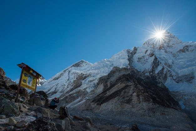 Trekker usar celular inteligente tirando foto da montanha do everest com everest acampamento base sig