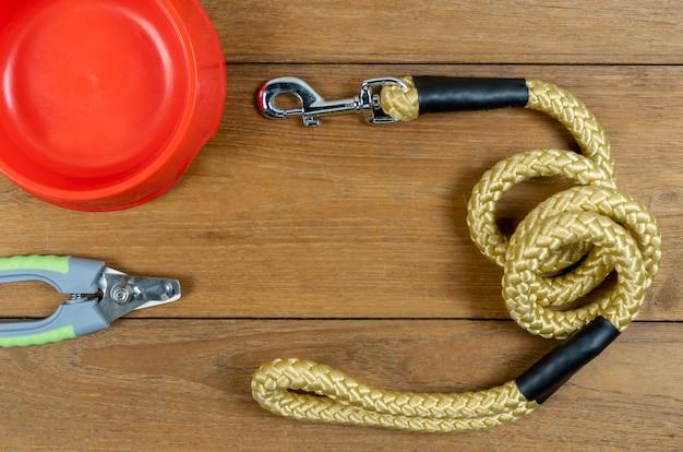 Trelas para animais de estimação e tigela de plástico e tesoura de unha na mesa de madeira