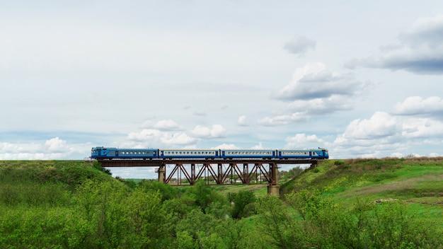 Trem a diesel. o trem de passageiros azul viaja em uma pista na grama. ferrovia no campo.