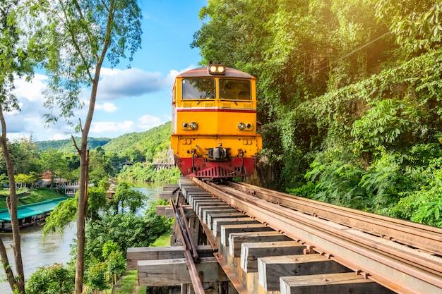 Trem antigo correndo na estrada de ferro de madeira em tham krasae