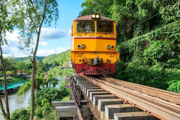 Trem antigo rodando na ferrovia de madeira em tham krasae, kanchanaburi, tailândia