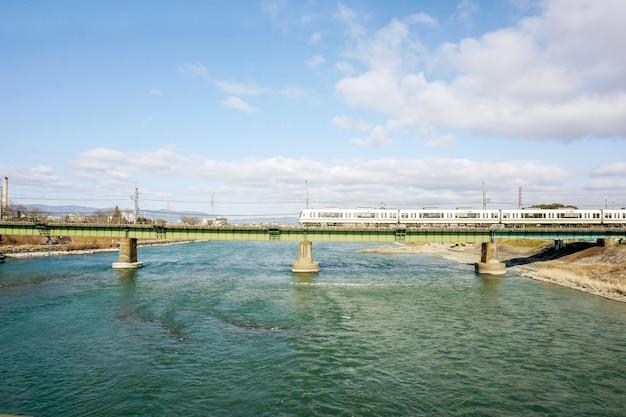Trem branco está atravessando um rio grande pela ponte sob o céu azul brilhante com nuvem