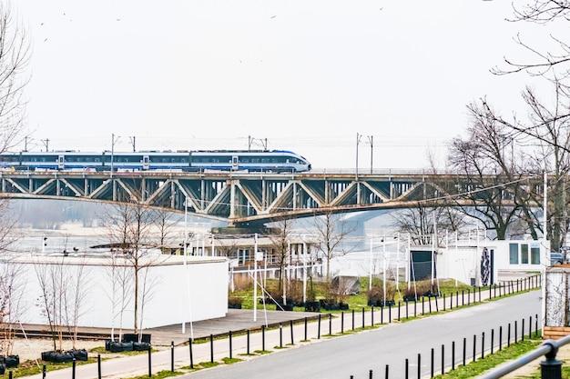 Trem de alta velocidade de passageiros em movimento através da ponte ferroviária acima do rio wisla