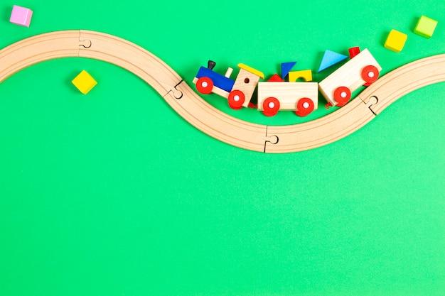 Trem de brinquedo de madeira com blocos coloridos e ferrovia de madeira sobre fundo verde claro.