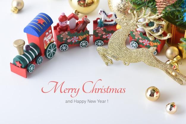Trem de brinquedo de madeira em feliz natal e feliz ano novo com bolas de celebração e outro de