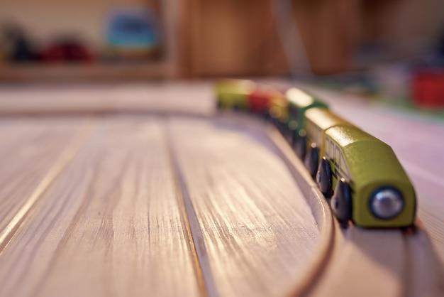 Trem de brinquedo de madeira em uma pista com quarto infantil desfocado no pano de fundo