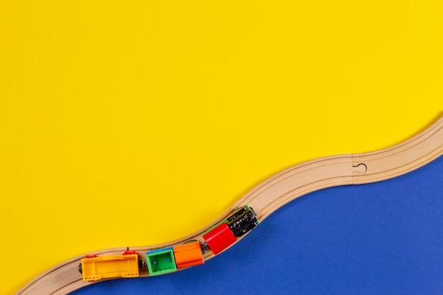 Trem de brinquedo e trilhos de madeira sobre fundo amarelo e azul