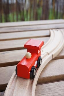 Trem de brinquedo vermelho de madeira em trilhos de madeira