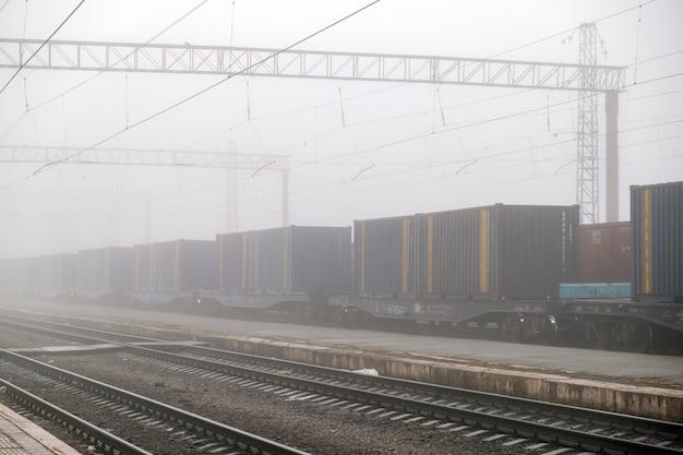 Trem de carga em movimento na plataforma de trem de carga, passando pela estação. passeios de vagões na ferrovia de aço. conceito de transporte de indústria pesada.