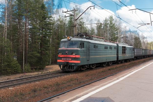 Trem de carga rebocado por uma locomotiva elétrica no fundo da floresta