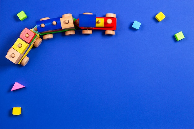 Trem de madeira do brinquedo com blocos coloridos sobre fundo azul. vista do topo