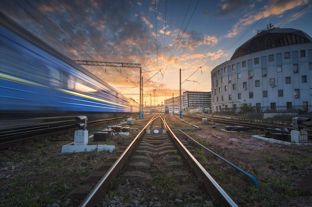 Trem de passageiros de alta velocidade em movimento na ferrovia ao pôr do sol