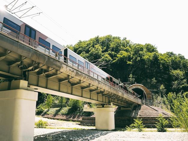 Trem de passageiros em túnel ferroviário na montanha