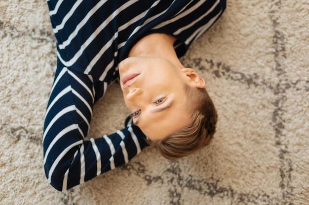 Trem de pensamentos. belo pensativo jovem de cabelos louros bem constituídos, deitado no chão, pensando e olhando ao longe