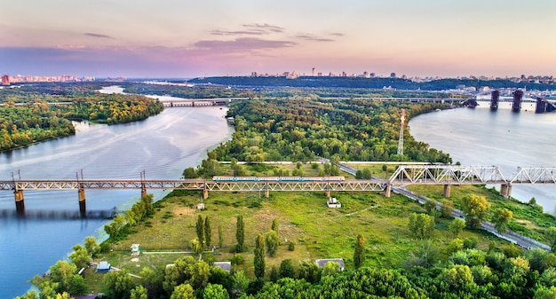 Trem elétrico urbano de kiev na ponte ferroviária de petrovsky, atravessando o rio dnieper, na ucrânia