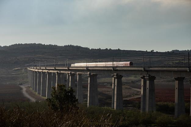Trem em uma ferrovia cercada por vegetação sob um céu azul nublado durante a noite