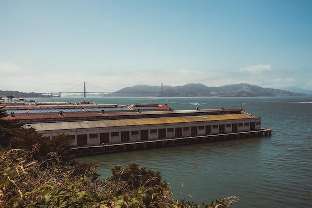 Trem marrom e branco na ponte ferroviária sobre a água durante o dia Foto gratuita