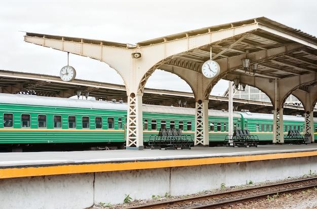 Trem passando por uma antiga estação com dois relógios pendurados no teto