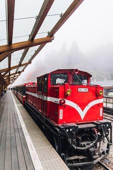 Trem vermelho na parada de alishan forest railway na plataforma da estação de trem de zhaoping em alishan, taiwan.