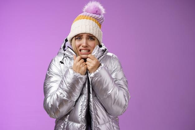 Tremendo desconfortável desagradou encantadora mulher loira sombria fofa em uma jaqueta prata elegante puxando o casaco bem