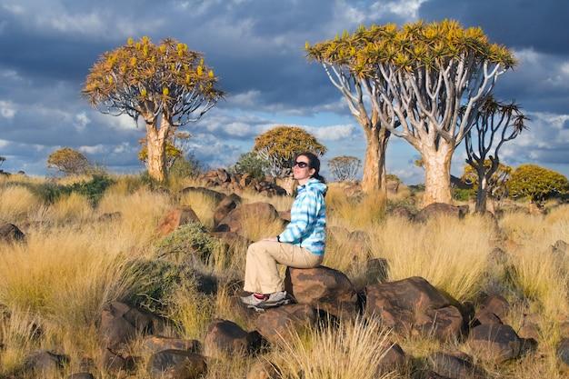 Tremer a paisagem da floresta da árvore, turista da mulher que olha a vista bonita. kokerbooms na namíbia, áfrica do sul. natureza africana