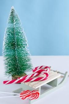 Trenó de madeira com bastões de doces e árvore de natal
