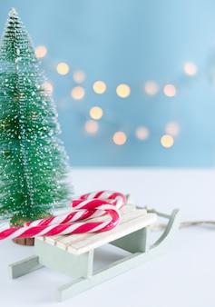 Trenó de madeira com doces e árvore de natal