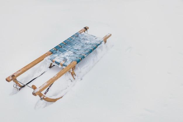 Trenó de madeira congelado na terra nevado na estação do inverno