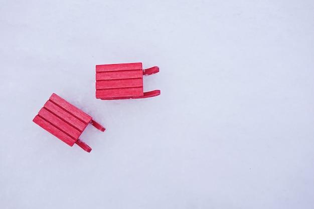 Trenó vermelho em miniatura na neve branca
