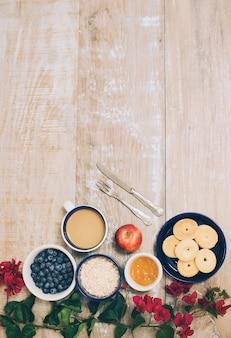 Trepadeira de flor de buganvílias com café e pequeno-almoço fresco saudável na mesa de madeira