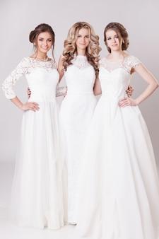 Três a noiva com cabelos bonitos e maquiagem posando e abraçando no estúdio. em vestidos de noiva