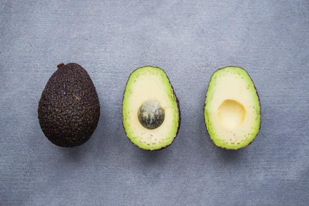 Três abacates verdes na mesa cinza