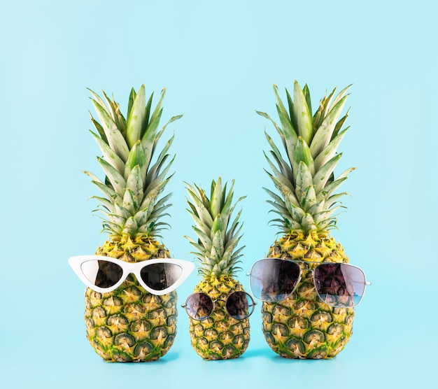 Três abacaxis com copos em forma de uma família de três de férias. conceito de viagens de verão para países tropicais