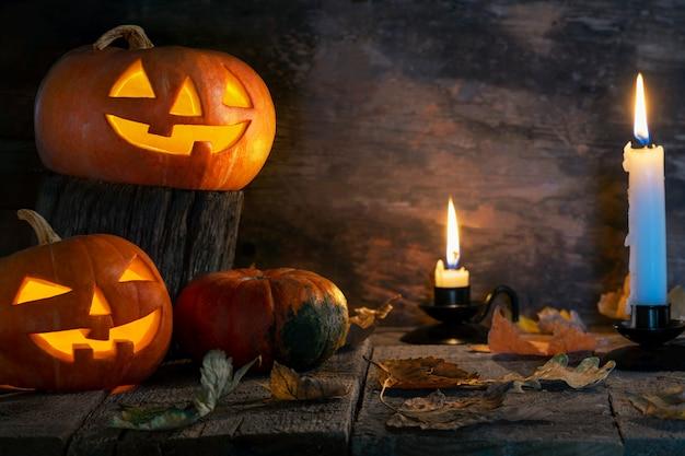 Três abóboras de halloween cabeça jack o lanterna na mesa de madeira
