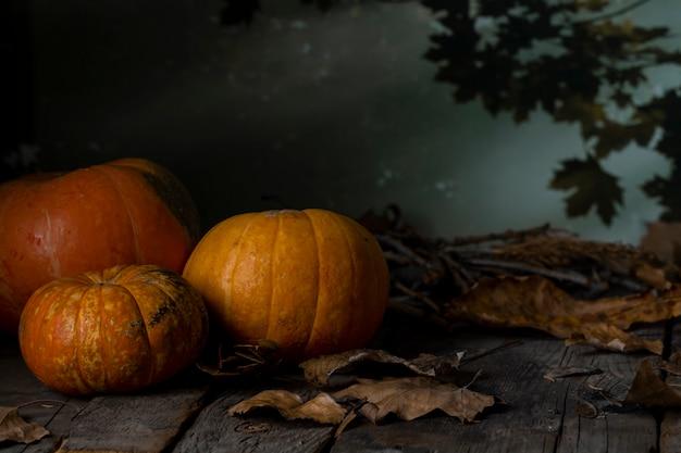 Três abóboras de halloween na mesa de madeira