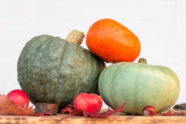 Três abóboras, maçãs e folhas de outono em uma mesa de madeira em um fundo branco