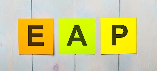 Três adesivos coloridos com o texto programa de assistência ao funcionário eap em um fundo de madeira azul claro