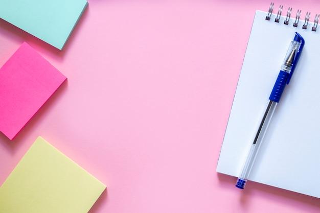 Três adesivos multicoloridos em uma delicada mesa rosa, um caderno branco com uma espiral e uma caneta azul