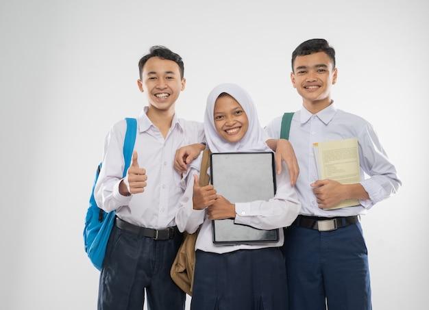 Três adolescentes com uniformes do ensino fundamental segurando um laptop com o polegar para cima enquanto o carregam ...