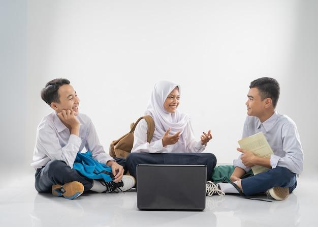 Três adolescentes com uniformes do ensino fundamental sentados no chão, estudando juntos e conversando com ...