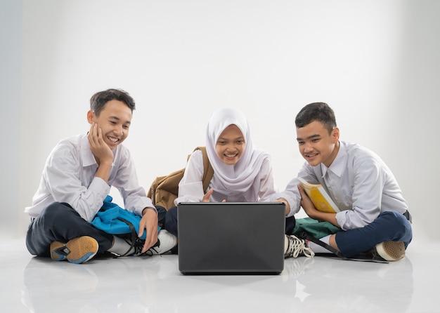 Três adolescentes com uniformes do ensino fundamental sentados no chão estudando juntos usando e olham ...