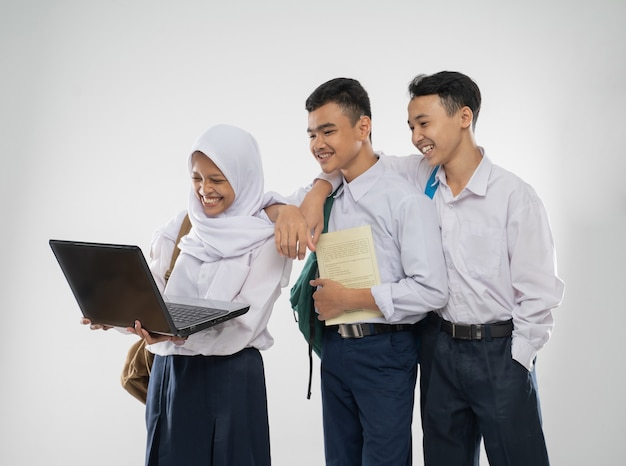 Três adolescentes com uniformes do ensino fundamental sorrindo, usando um laptop juntos, enquanto carregam ...