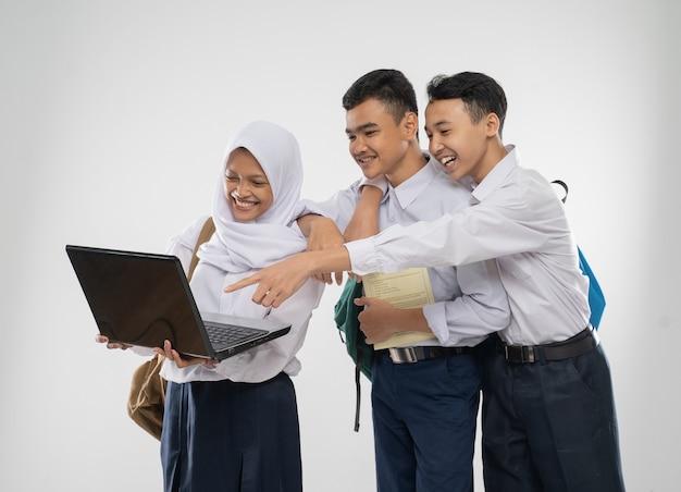 Três adolescentes com uniformes do ensino fundamental, usando um laptop junto com a mochila escolar e ...