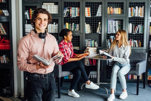 Três adolescentes conversando sobre o projeto, trabalhando juntos na sala da biblioteca