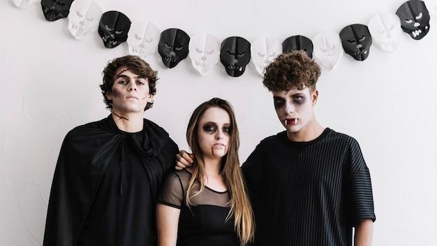 Três adolescentes em fantasias de vampiros e zumbis