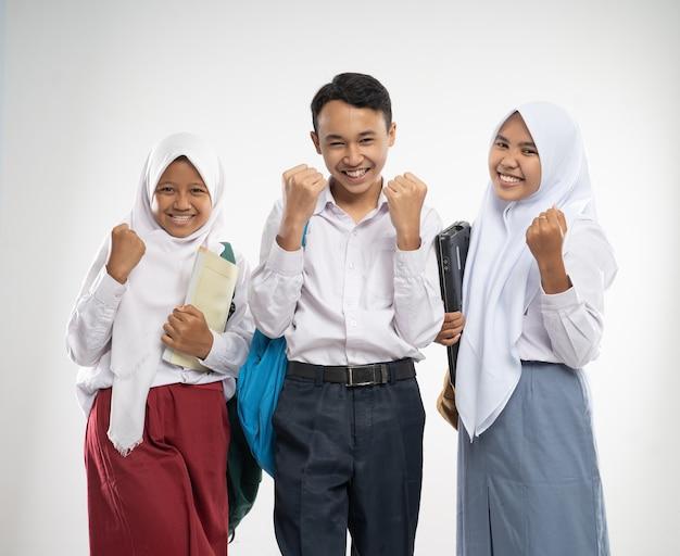 Três adolescentes em uniformes escolares sorriam com gestos animados ao carregar uma mochila e um ...